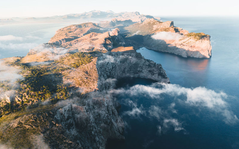 aerial view over the coastline at Cap de Formentor – moody sunrise Beauty In Nature Water Scenics - Nature Sea Nature Sky Rock Land Rock - Object Cloud - Sky Rock Formation Outdoors Travel Foggy Clouds And Sky Aerial View Aerial Photography Coastline SPAIN Mallorca Landscape Formation