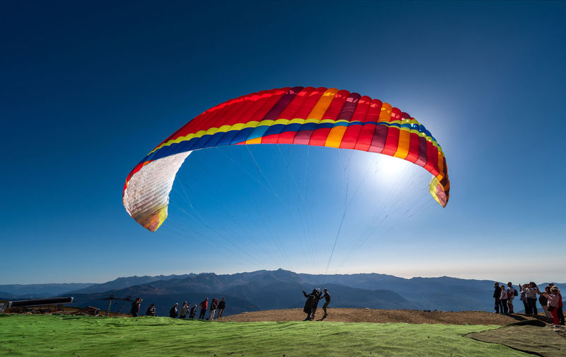 People flying kite against clear blue sky