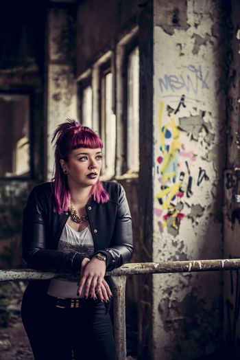 Thoughtful woman looking away while leaning on railing in abandoned building