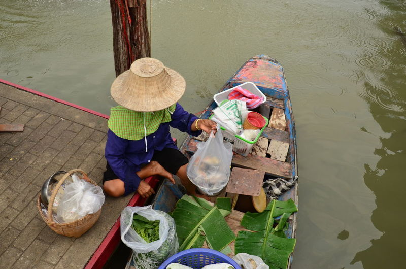 High angle view of vendor arranging objects in boat for floating market