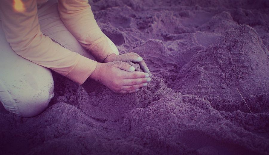 Midsection of woman making sandcastle at beach
