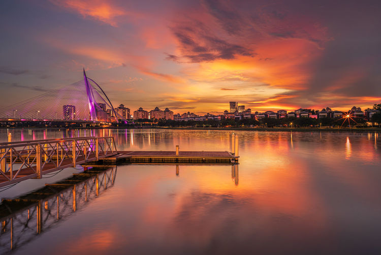Illuminated bridge over river against sky during sunset