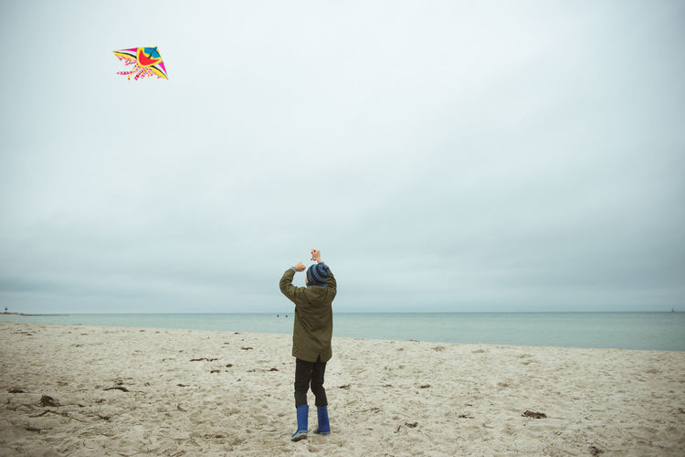 Rear view of boy holding kite standing on beach against sky