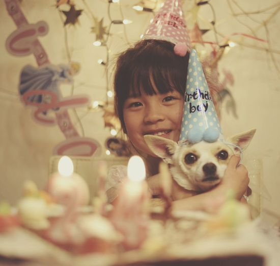 Portrait of cute smiling girl holding dog while sitting by birthday cake at home