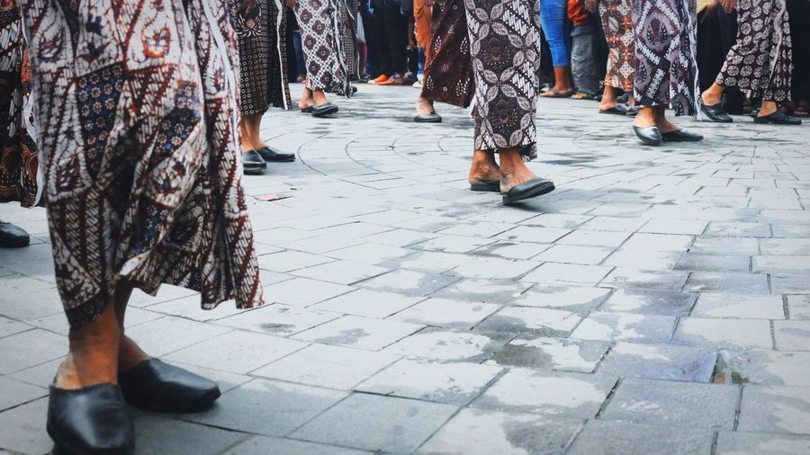 Low section of people wearing traditional clothing standing on footpath