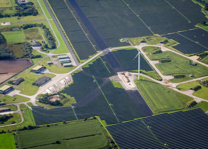 High angle view of solar panels and wind turbine on field