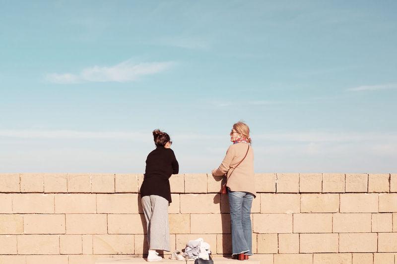 Friendship Togetherness Men Bonding Standing City Young Women Sunlight Women Copy Space Brick Wall