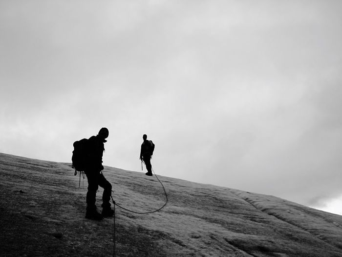 Full length of hikers on mountain against sky