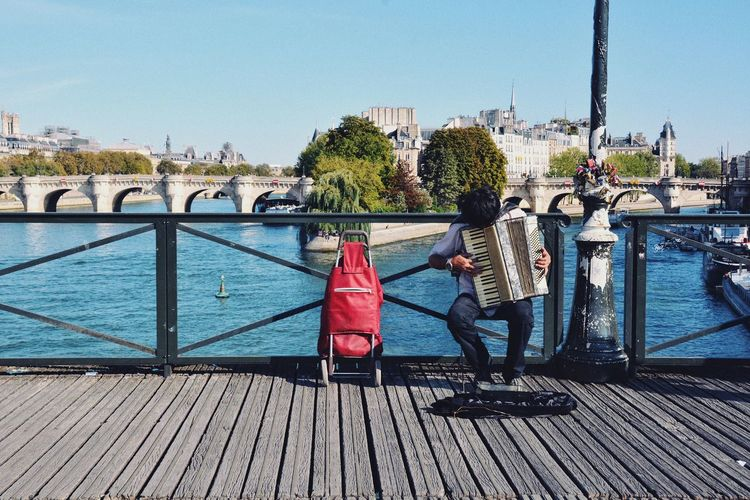 """He played """"La Vie en rose"""". Travel Accordeon Playing Music Paris Cliche Romantic Street Artist Music Sunlight Water Real People Nature Full Length Sky Architecture Lifestyles Men Human Connection"""