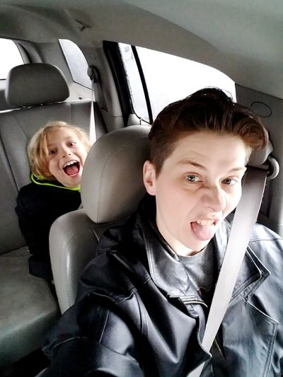 Portrait of playful mother and son traveling in car