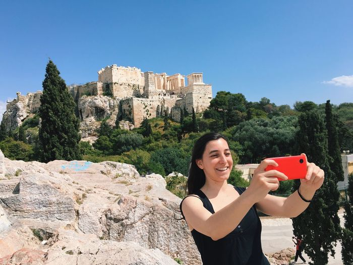 Happy woman taking selfie while standing by rocks against acropolis of athens