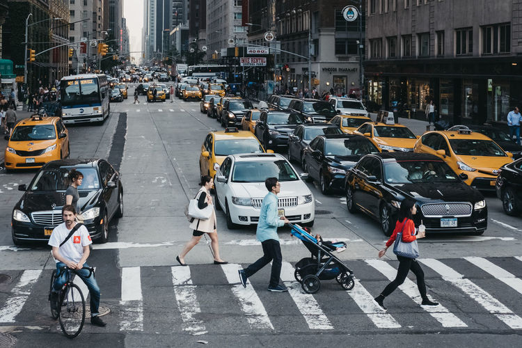 Top view of people crossing the road in Manhattan, New York, USA. New York New York City USA United States Travel Tourism Stroller Commute Pedestrian Crosswalk City Street Crossing Group Of People City Life Road Street City Transportation Car Traffic Real People City Life Young People Everyday Life Big City Life