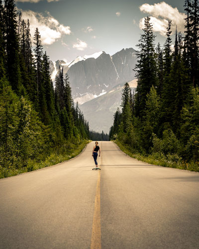 Rear view of woman skateboarding on road against mountain