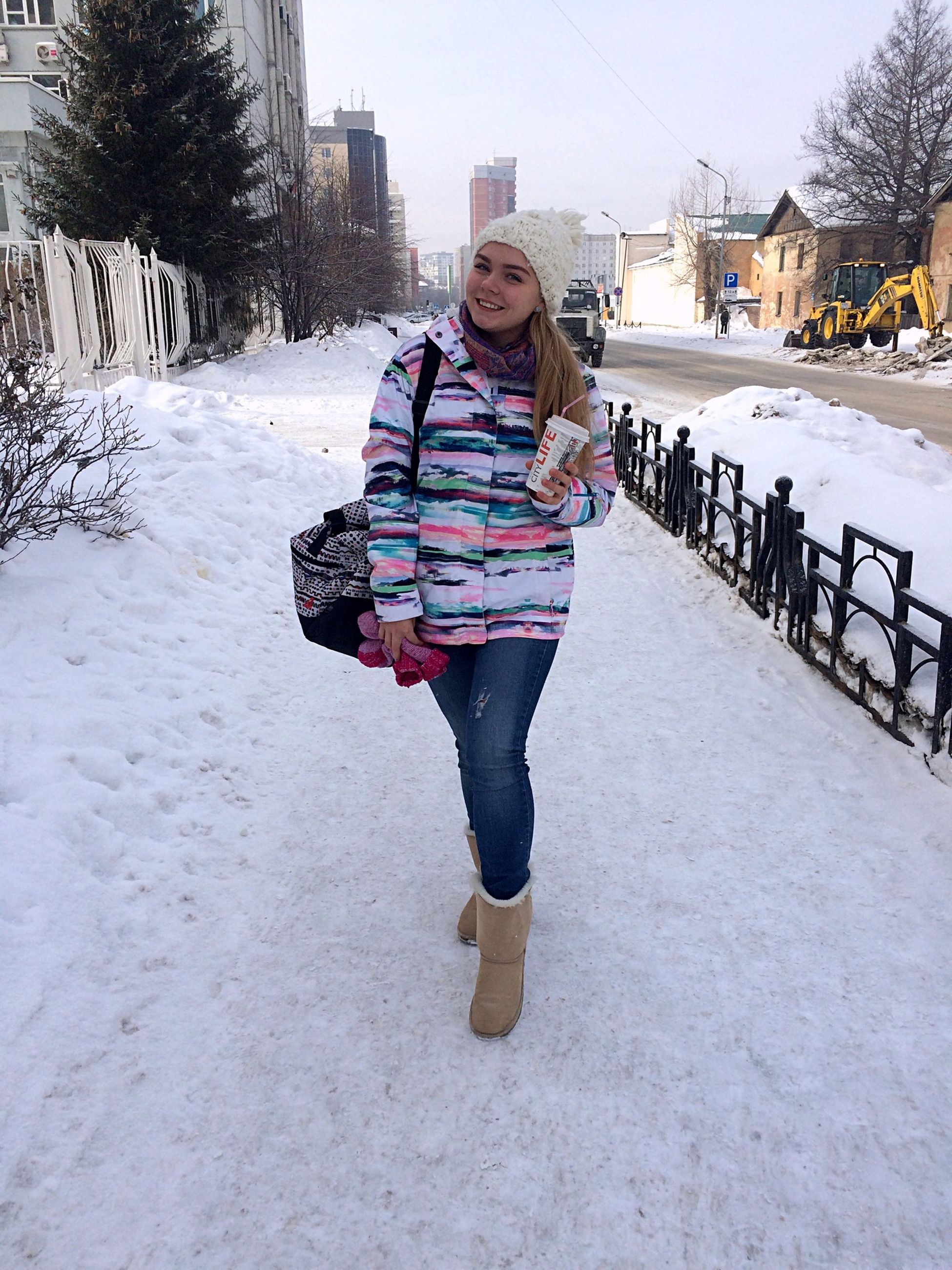 full length, lifestyles, winter, person, casual clothing, leisure activity, snow, cold temperature, warm clothing, season, building exterior, front view, built structure, young adult, standing, architecture, street, looking at camera