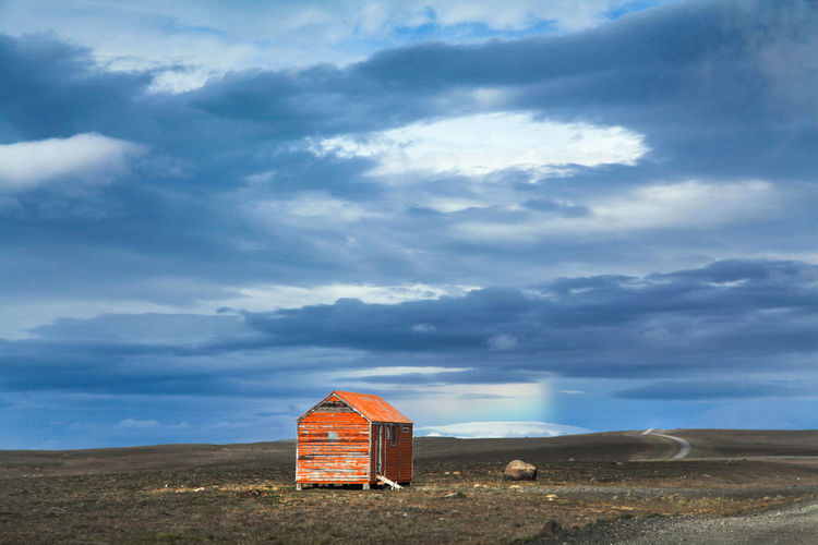 Abandoned hut against cloudy sky