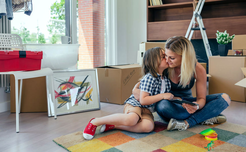 Mother and son playing the tablet and kissing sitting on the carpet Family Fun Happiness Happy Horizontal Mother Moving Tablet Unpacking Woman Boxes Boy Cardboard House Indoors  Kid Kissing Lifestyles Living Room New Home Packing Placing Real People Relocating Two People