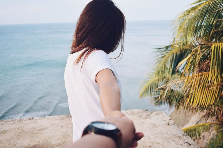 Cropped image of man holding woman hand on retaining wall by sea
