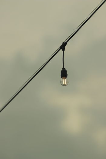 Low angle view of light bulb against sky