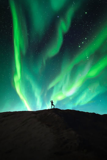 Low angle view of man standing on landscape against aurora bolearis in sky at night