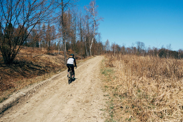 Full length of woman riding bicycle in forest