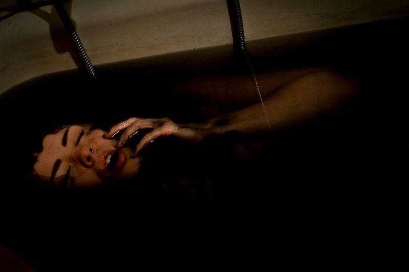 Woman Lying In Bath Of Black Water