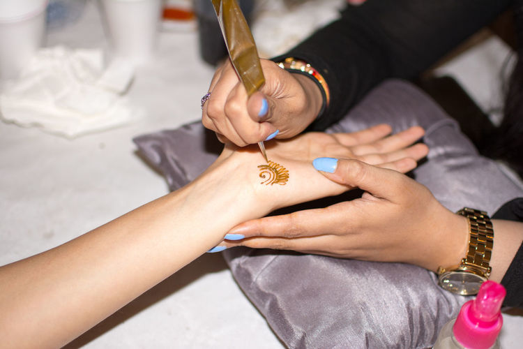 Cropped image of artist making henna tattoo on woman hand