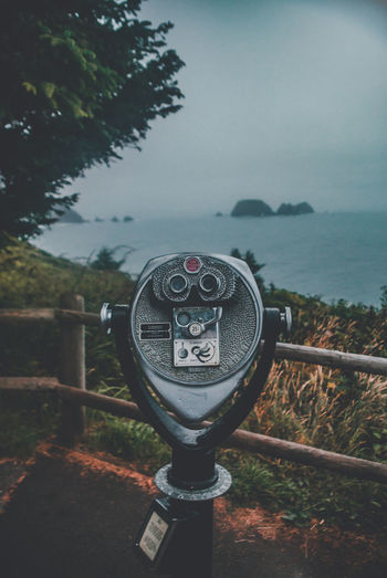 Close-up of coin-operated binoculars by river against sky