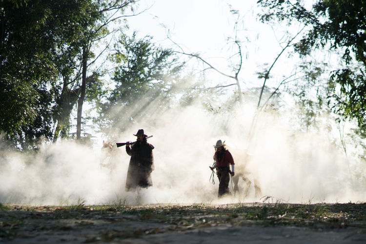Men standing in forest amidst smoke