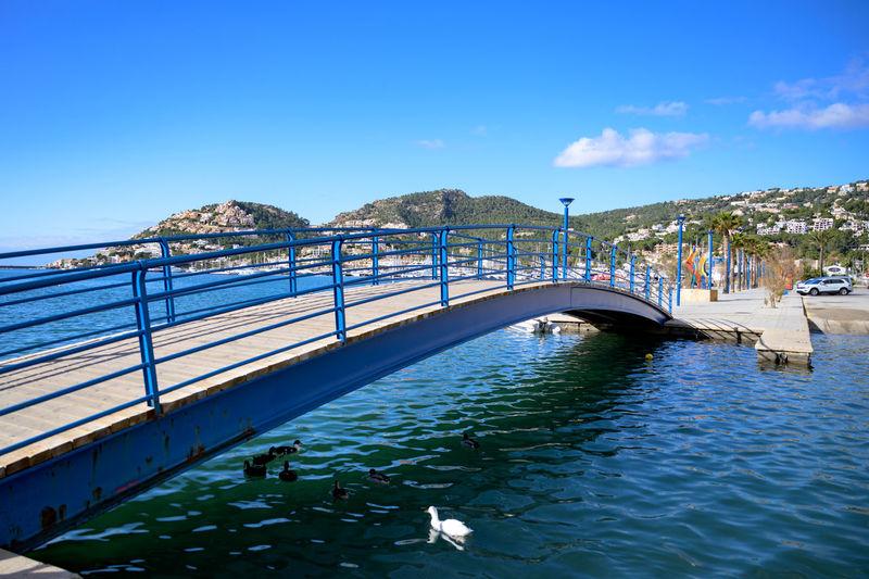 Bridge over sea against blue sky