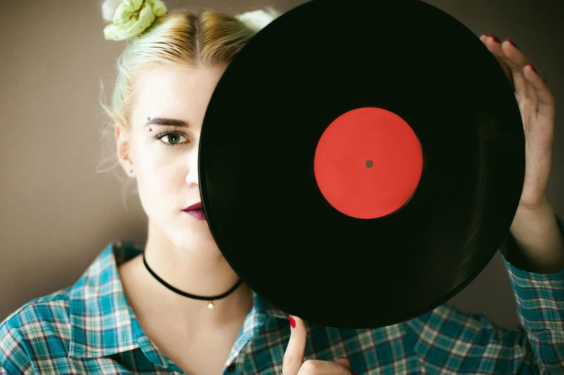 Portrait Of Young Woman Holding Vinyl Record While Standing At Home