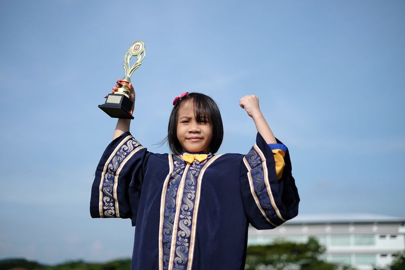 Portrait of confident girl with trophy against sky