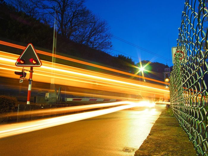 Blurred Motion Car City Clear Sky Crossing Dusk Highway Illuminated Light Trail Long Exposure Motion Night On The Move Outdoors Railroad Crossing Railroad Track Road Road Sign Rush Hour Sky Speed Street Light Traffic Train Transportation