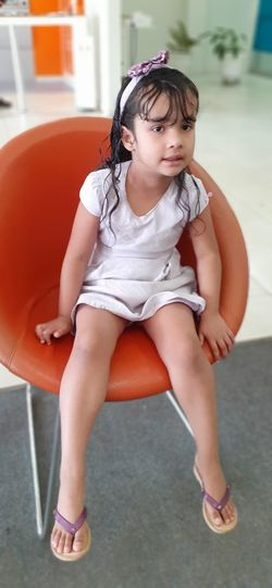 Full length of girl sitting on chair at home