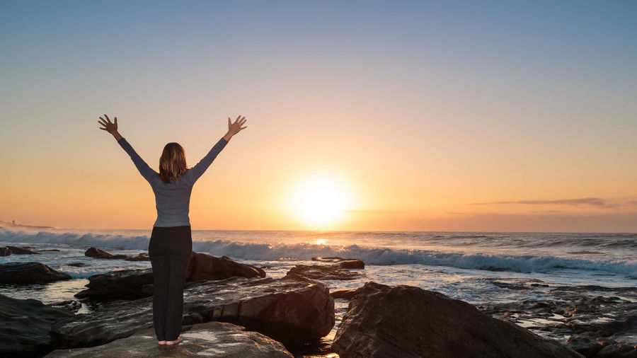 Rear view of woman exercising yoga with hands raised on rock at beach against sky during sunrise