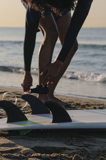 Surfer preparing to surf on the beach at sunrise person