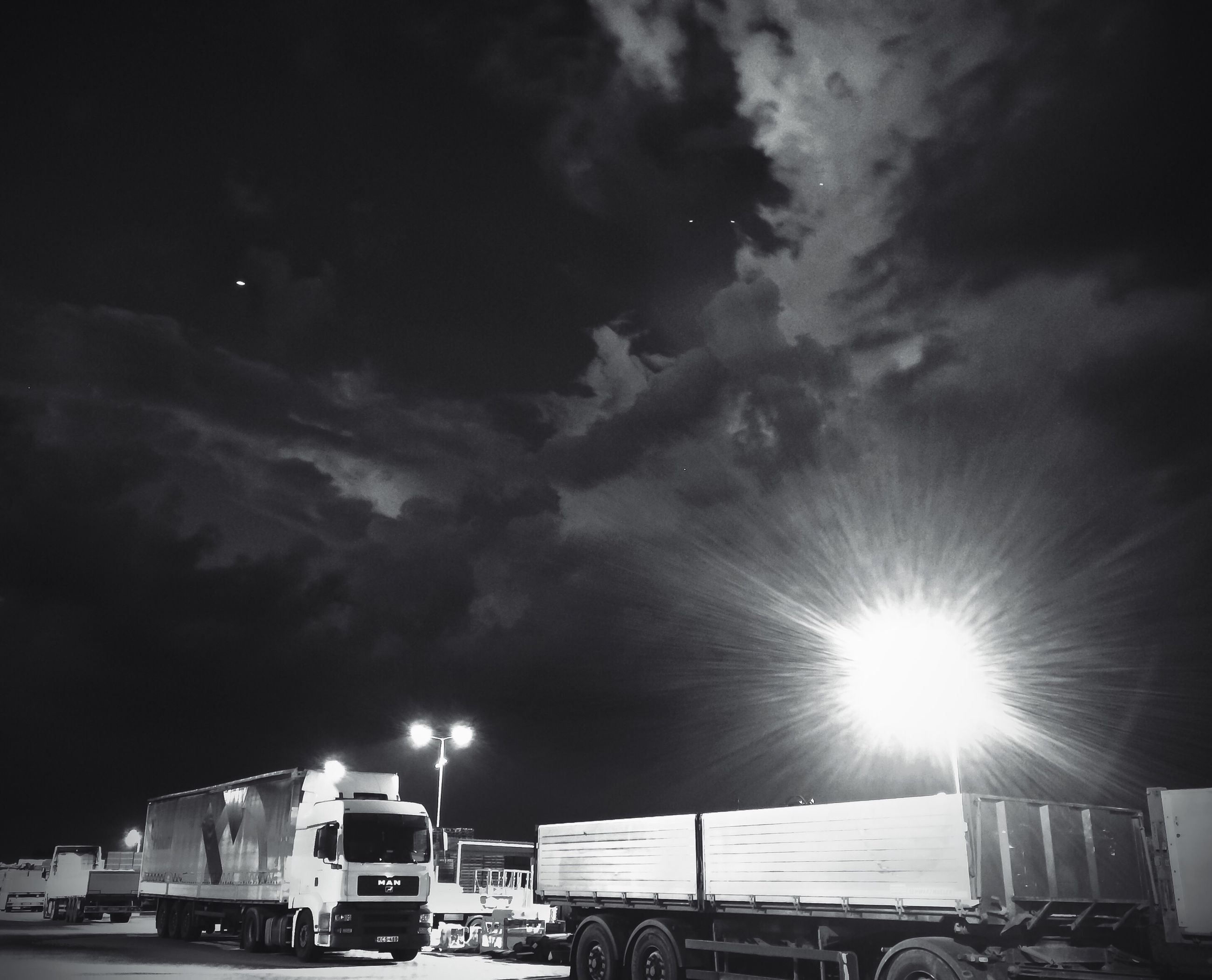 sky, built structure, cloud - sky, transportation, architecture, building exterior, night, car, illuminated, mode of transport, street light, low angle view, land vehicle, cloudy, outdoors, weather, cloud, no people, nature, lens flare