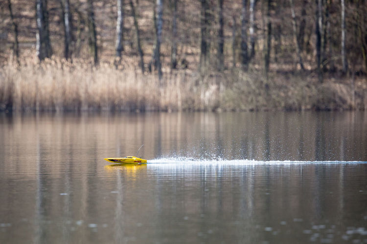 Yellow Toy Boat Sailing In Lake Against Trees