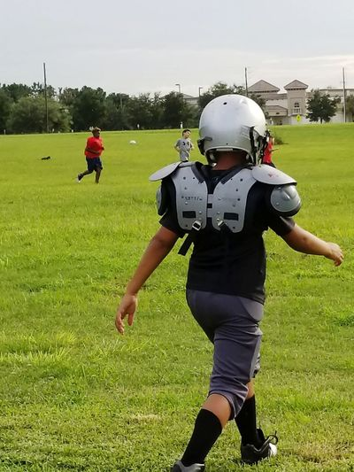 Headwear American Football - Sport American Football - Ball Sports Helmet American Football Player Sport Competition Protection Football Helmet Teamwork Sports Team American Football Field Grass Full Length Sports Clothing Green Color People Helmet Competitive Sport Standing