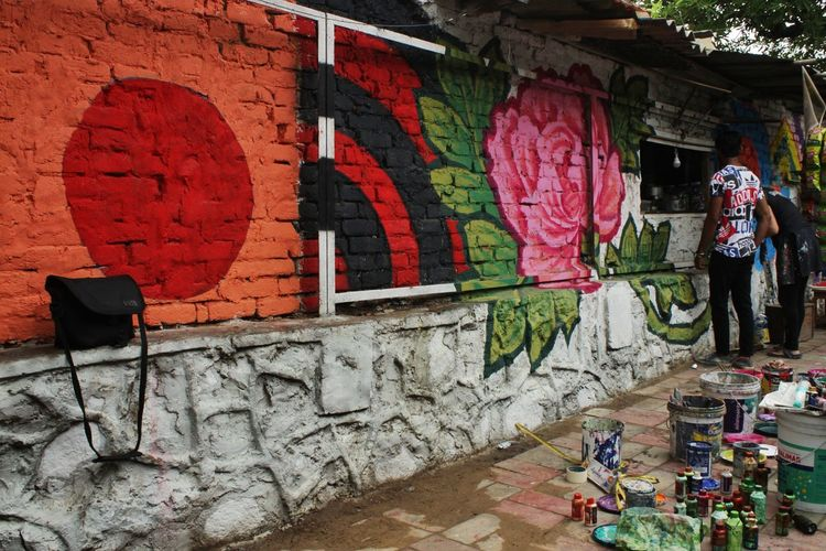Rear view of people walking against graffiti wall