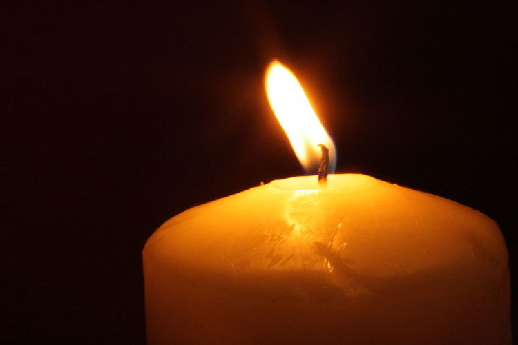 Close-up of lit candle in dark room