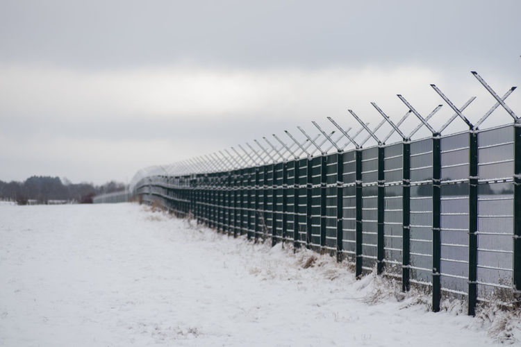 Fence against sky during winter