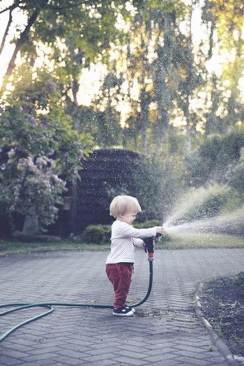Full length of cute girl holding garden hose