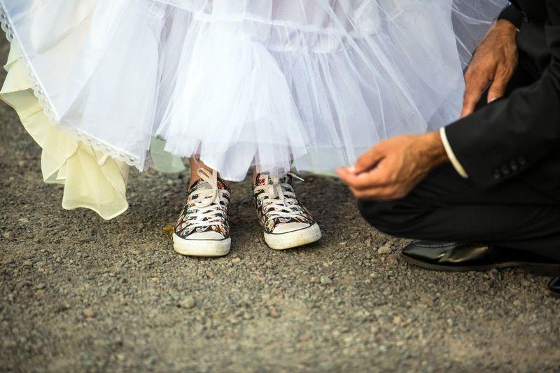 Low Section Of Bridegroom Adjusting Bride Wedding Dress