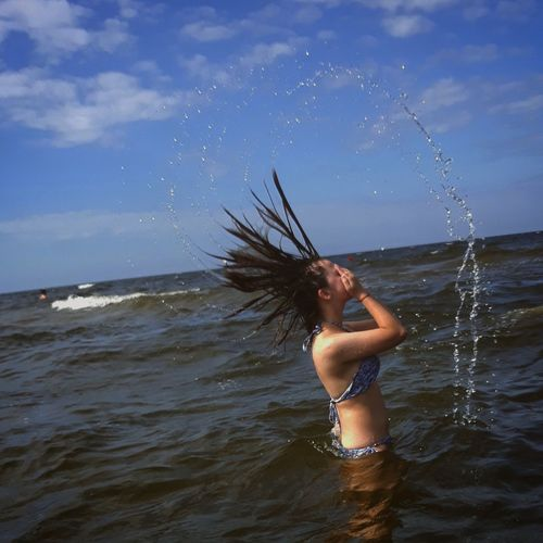 Side view of teenage girl tossing wet hair in sea against sky