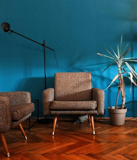 Chairs and tables against blue wall at home