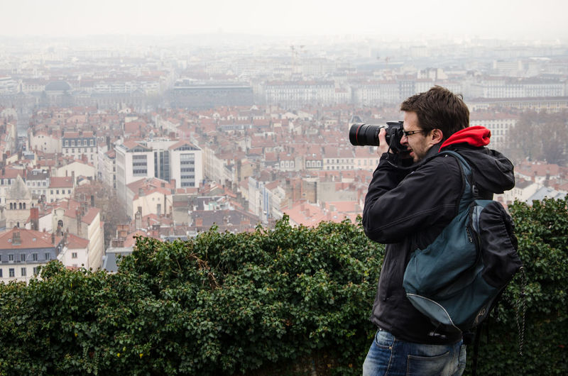 Side view of man photographing cityscape through camera
