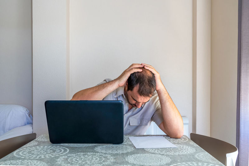 Frustrated man using laptop sitting at home