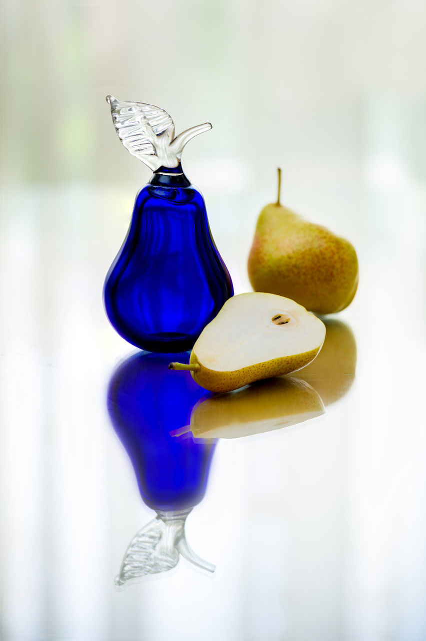 still life, focus on foreground, no people, indoors, close-up, freshness, healthy eating, food, food and drink, fruit, blue, wellbeing, table, glass - material, selective focus, creativity, yellow, day, reflection, pear