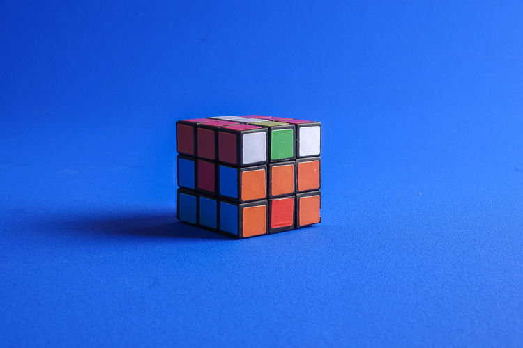 RUBIK'S CUBE , CREATIVITY TOY Creativity Rubik Cube Block Blue Blue Background Box Close-up Colored Background Copy Space Cube Shape Geometric Shape Indoors  Intelligence Leisure Games Multi Colored No People Red Rubik Shape Stack Still Life Studio Shot Table Toy