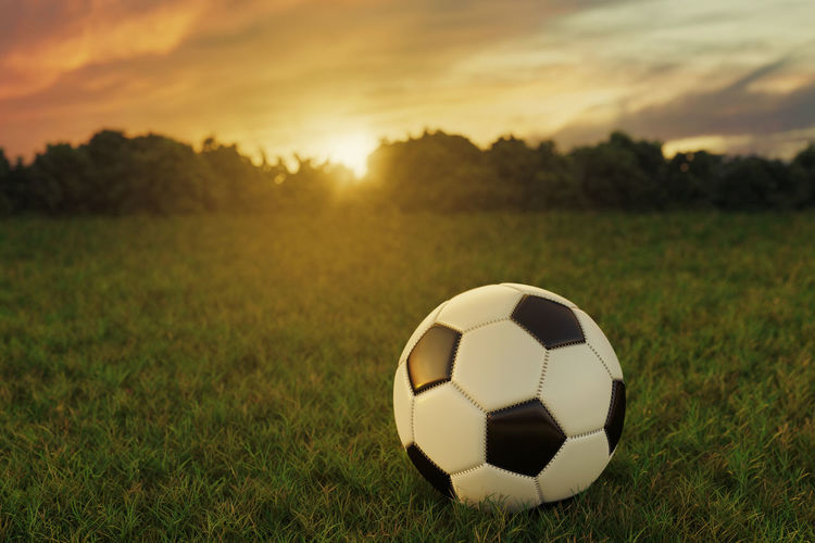 Close-up of soccer ball on field during sunset